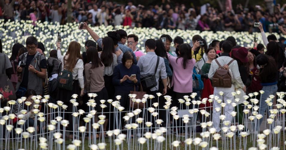 """14.fev.2016 - Visitantes da instalação de arte pública """"Light Rose Garden"""" tiram fotos em Tamar Park, Hong Kong. A obra é composta por 25.000 rosas brancas feitas de luzes LED, que representam a continuidade das tradições românticas do Valentine's Day (Dia dos Namorados em vários países) e do Festival das Lanternas da China no último dia do período de Ano Novo chinês"""