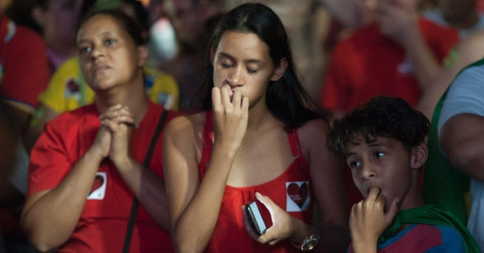 17.abr.2016 - Menina rói as unhas enquanto acompanha votação na Câmara dos Deputados, durante ato na praça da Estação, em Belo Horizonte