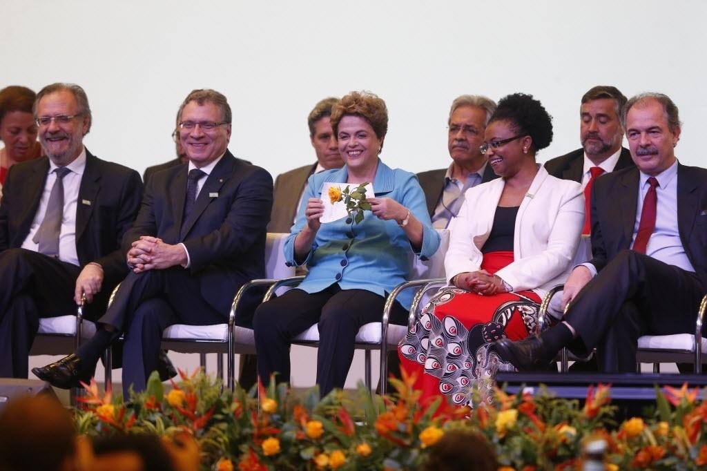 27.abr.2016 - A presidente Dilma Rousseff mostra flor e desenho que ganhou antes da abertura das Conferências Conjuntas de Direitos Humanos, em Brasília