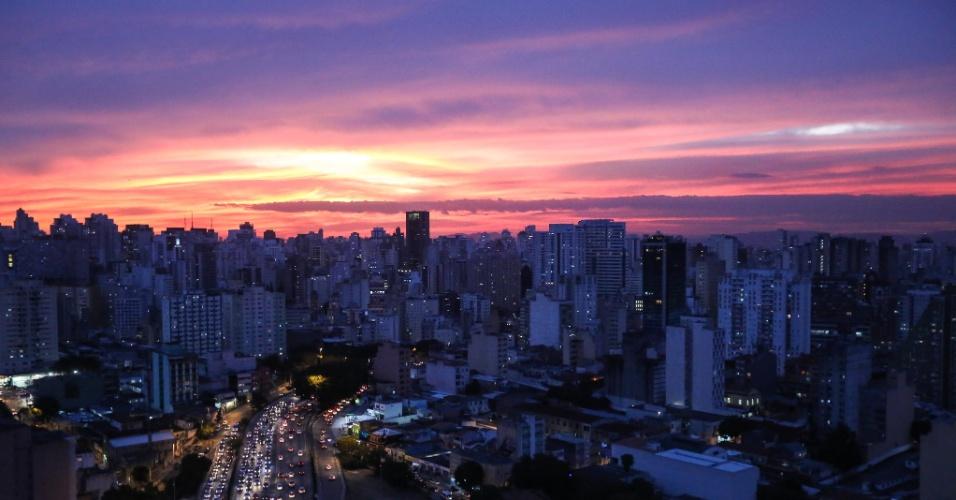 30.jun.2016 - O céu da cidade de São Paulo fica colorido durante o pôr do sol no bairro da Bela Vista, na região central