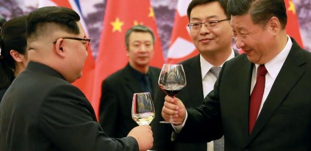 Líder norte-coreano, Kim Jong-un, e o presidente chinês, Xi Jinping, brindam durante jantar no grande salão do povo em Pequim - KCNA/AFP