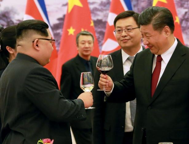 26.mar.2018 - Líder norte-coreano Kim Jong-un e o presidente chinês Xi Jinping brindam durante jantar no Grande Salão do Povo, em Pequim