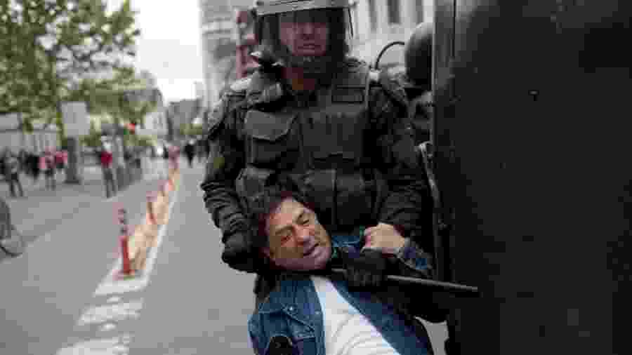 19.out.2019 - Policial usa bastão para deter manifestante pelo pescoço durante protestos em Concepción, no Chile - Juan Gonzalez/Reuters