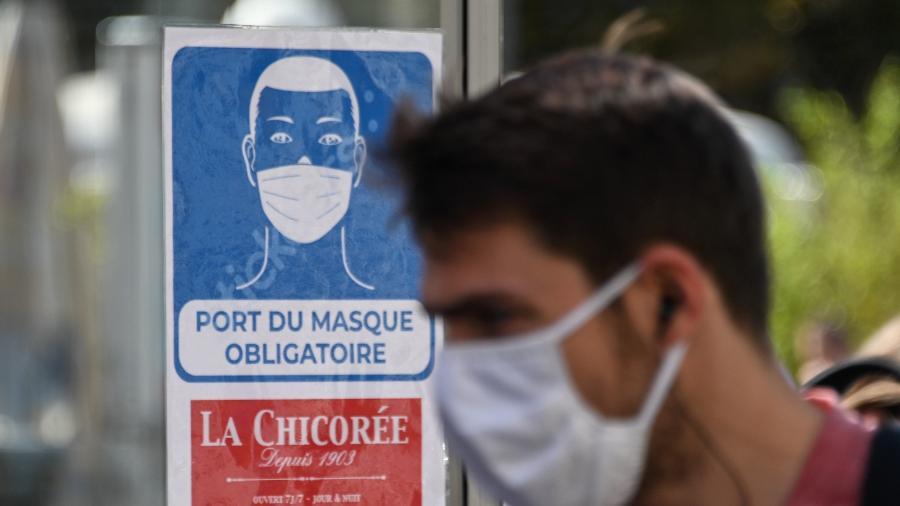 Homem usando máscara passa por uma placa que informa sobre uso obrigatório do acessório em loja em Lille, na França  - Denis Charlet/AFP