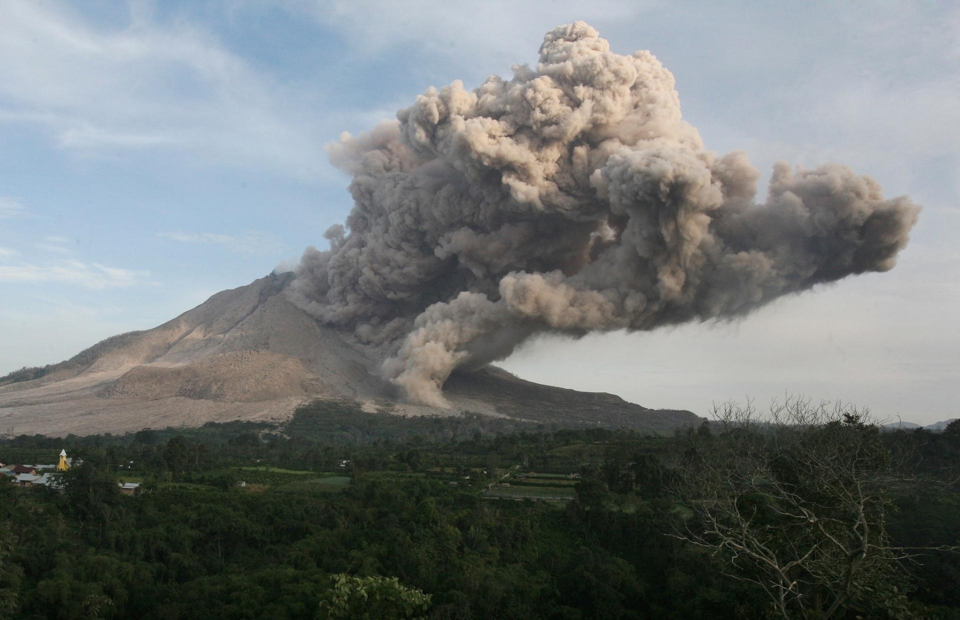 29.jun.2015 - Vulcão Sinabung expele cinzas durante erupção, vista do vilarejo de Beras Tepu, no norte de Sumatra, na Indonésia, nesta segunda-feira (29). Mais de 10 mil pessoas de 12 vilarejos deixaram suas casas e foram removidas para campos de refugiados, devido a erupção do vulcão