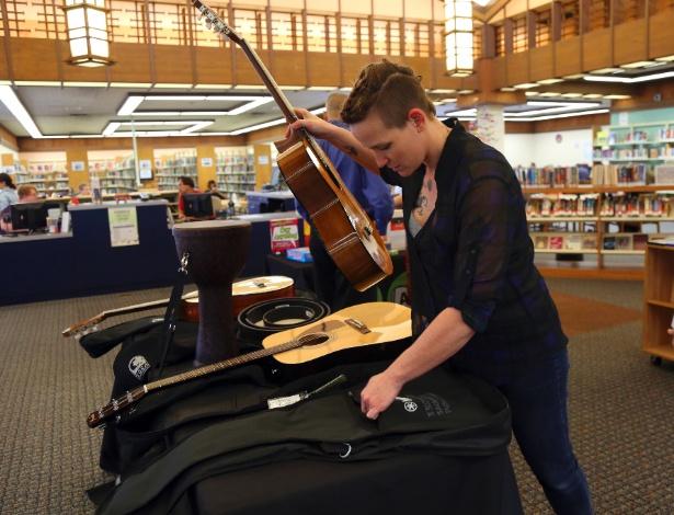 """Jessica Zacker, da equipe da Biblioteca Pública de Sacramento, arruma violões que fazem parte do projeto """"Biblioteca das Coisas"""" em Sacramento, na Califórnia, EUA - Jim Wilson / New York Times"""