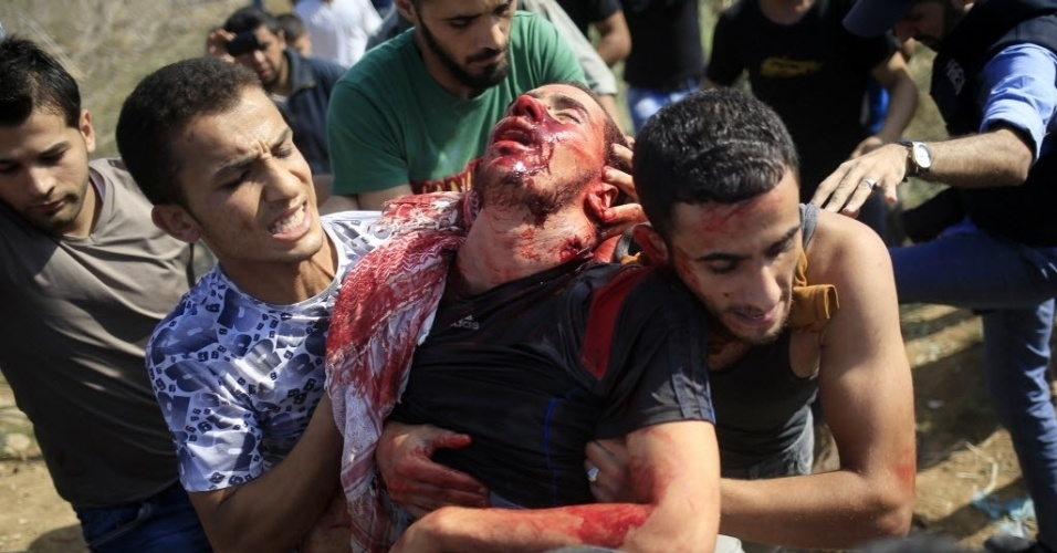 9.out.2015 - Manifestante palestino é retirado por companheiros depois de ter sido ferido durante confrontos com as forças de segurança israelenses perto da fronteira entre Israel e a faixa de Gaza. Pelo menos cinco palestinos morreram e mais de 30 ficaram feridos durante os confrontos. Em Gaza, o líder do Hamas, Ismail Haniyeh, afirmou que a violência atual é uma nova Intifada, a exemplo da revolta palestina de 1987 e 2000