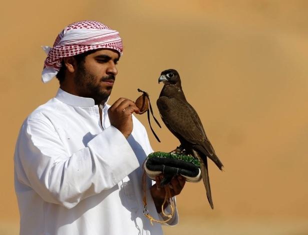 6.jan.2016 - Homem treina falcão durante o Festival da Duna de Moreeb, no deserto de Liwa, nos Emirados Árabes Unidos. O evento atrai participantes de todo a região do Golfo para exibições de carros, motos, falcões, camelos e cavalos e outras atividades destinadas a promover a cultura local