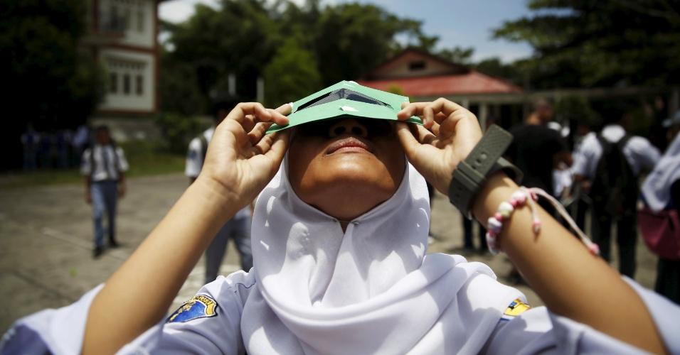 7.mar.2016 - Estudante de ensino médio da cidade de Ternate island, na Indonésia, testa filtro de raios solares produzido em oficina promovida em parceria com a Sociedade Astronômica de Hong Kong. Assim como na maior parte do hemisfério oriental, no país será possível observar o eclipse solar parcial previsto para a próximo quarta-feira