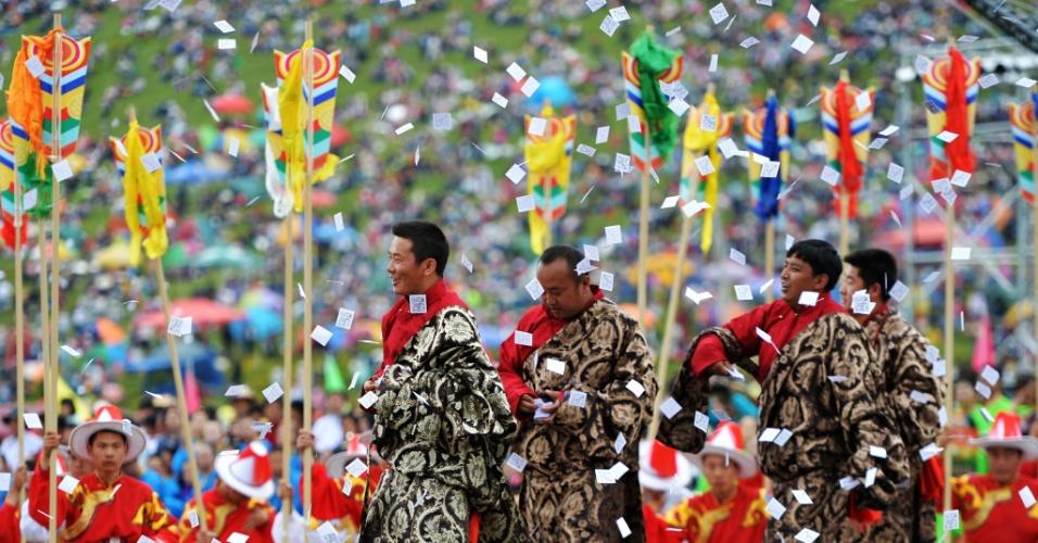 17.jul.2016 - Seguindo a tradição local, público joga papéis impressos com a imagem de um cavalo durante a abertura do festival turístico de Shambhala, na cidade de Gannan, no Tibete