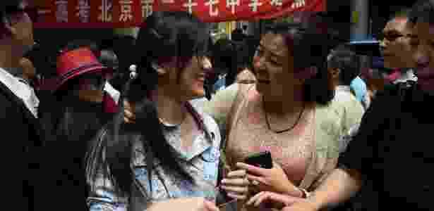 """Jovem conversa com familiares após prestar o """"gaokao"""", o """"Enem"""" dos chineses, em 7 de junho de 2016 - Greg Baker/AFP"""