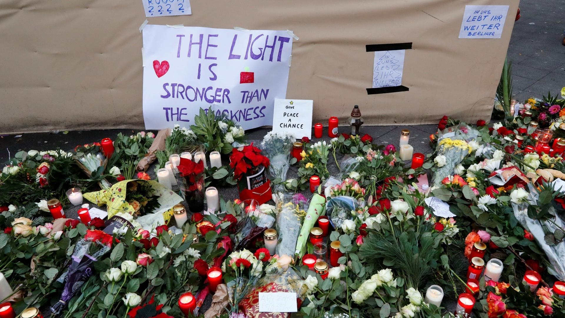 20.dez.2016 - Flores e cartazes são colocados ao lado do mercado natalino em homenagem às vítimas do caminhão que invadiu a feira de Berlim, na Alemanha, nesta segunda-feira (19)