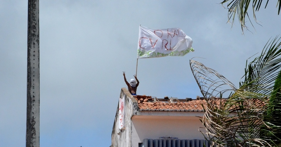 18.jan.2017 - Preso exibe bandeira de facções do alto do telhado de um dos pavilhões do presídio Alcaçuz, em Nísia da Floresta (RN)