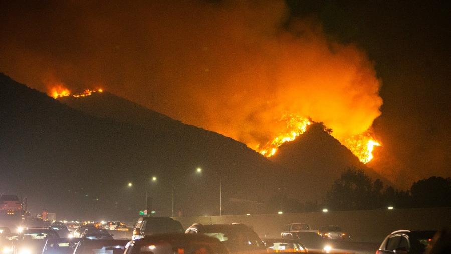 Trânsito em via de Los Angeles, com incêndio ao fundo - Qian Weizhong/Xinhua