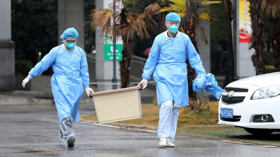 Pesquisadores carregam caixa no Hospital Jinyintan, na China - Reuters