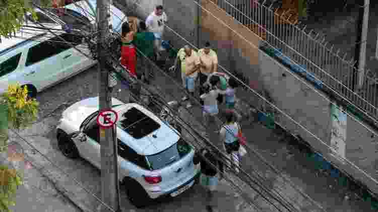 30.mai.2020 - Um homem de camisa amarela (no lado direito da foto) se aproximou e agrediu o morador (de verde) pelas costas, dando início a mais uma confusão. Luiz Eduardo segue de costas, no celular - Reprodução - Reprodução