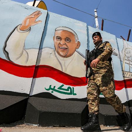 1.mar.2021 - Militar iraquiano caminha armado em frente a um mural com a imagem do papa Francisco em Bagdá, no Iraque; pontífice inicia hoje uma visita histórica ao país - Sabah Arar/AFP