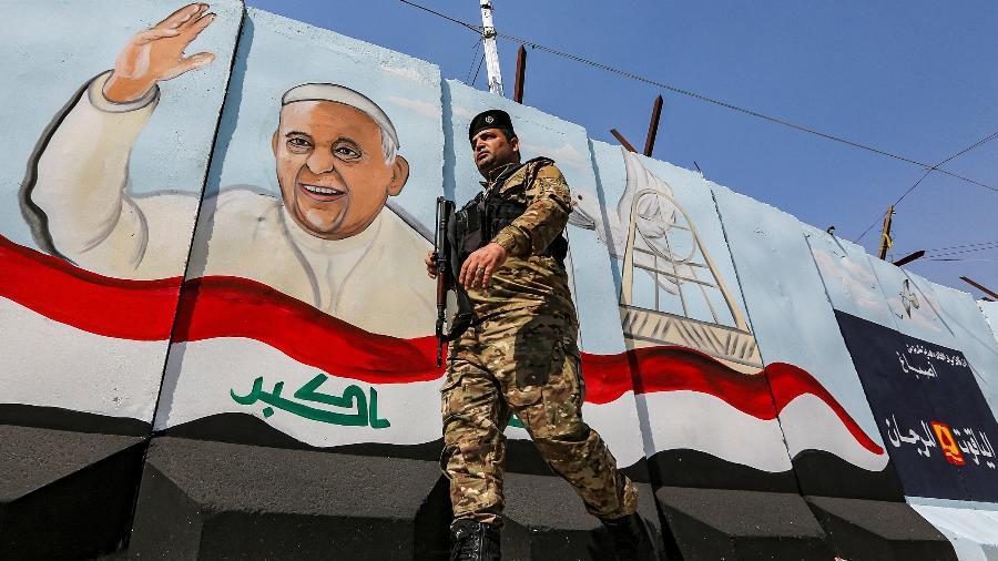 1.mar.2021 - Militar iraquiano caminha armado em frente a um mural com a imagem do papa Francisco em Bagdá, no Iraque - Sabah Arar/AFP