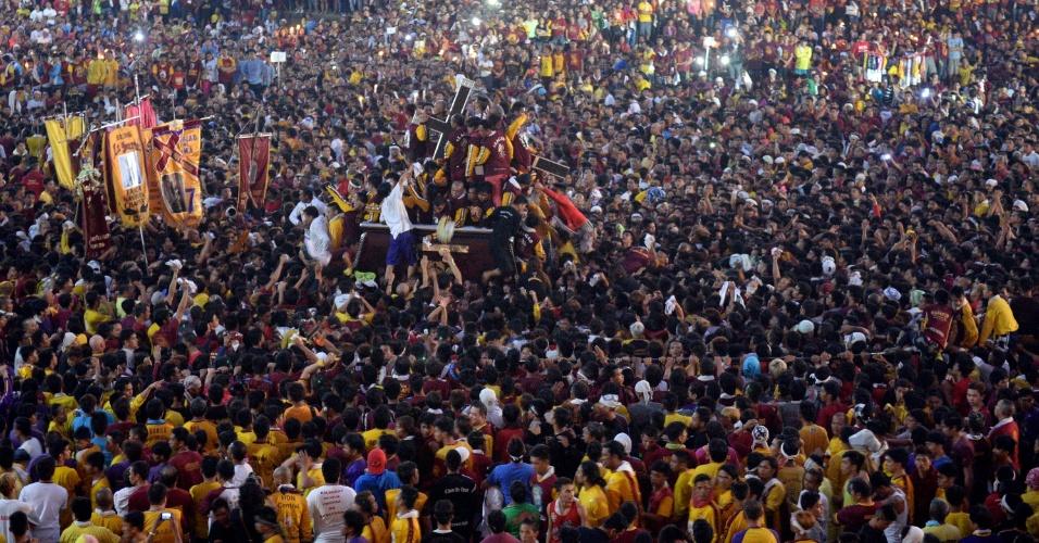 9.jan.2016 - Devotos lutam parar tocar a estátua do Nazareno Negro no início da procissão religiosa anual em Manila (Filipinas). Homens e mulheres se jogam sobre a multidão para tocar o ícone de Jesus Cristo na procissão, que é considerada um dos maiores festas católicas do mundo