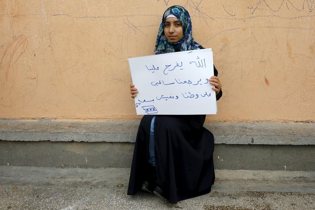 A refugiada síria Kamer Topalca, 18, segura um cartaz que diz: