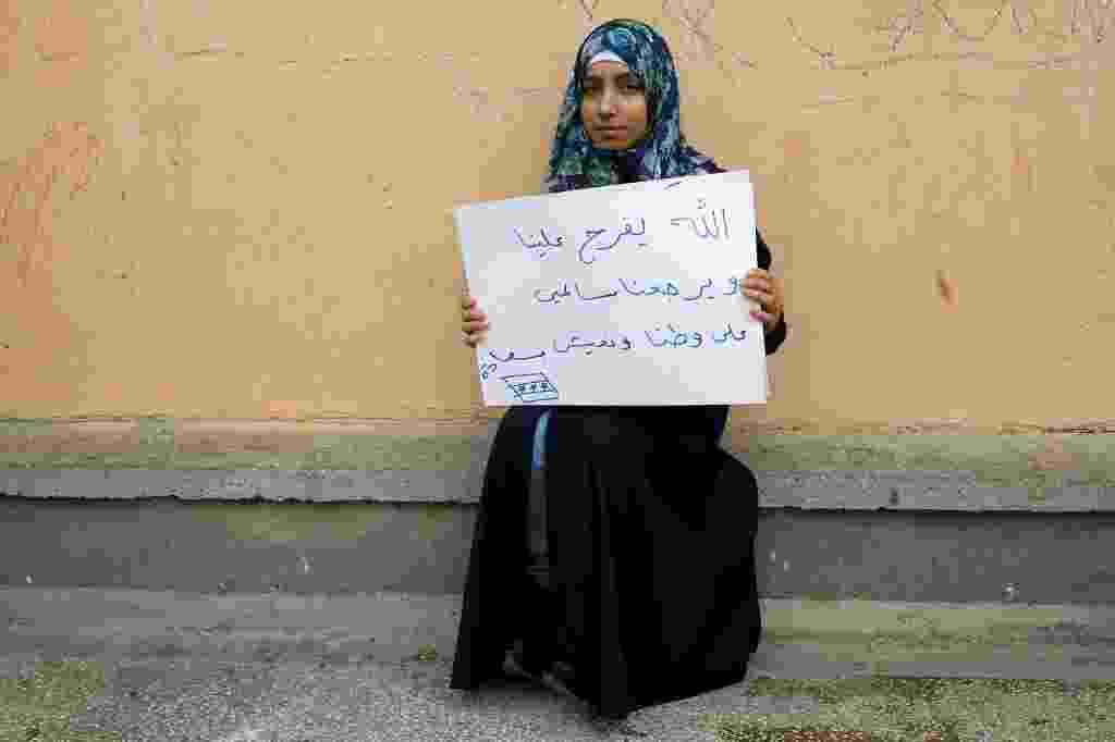 """A refugiada síria Kamer Topalca, 18, segura um cartaz que diz: """"Meu Deus nos salve. Deixe-nos retornar à nossa pátria em segurança. Deixe-nos vivermos felizes"""". Atualmente ela vive no campo de refugiados de Yayladagi, na província de Hatay, na Turquia, perto da fronteira com Síria. A guerra civil na Síria, que já deixou centenas de milhares de mortos, empurra outros tantos para o exílio, entre muitos deles crianças. Os desenhos das crianças do acampamento mostram memórias de suas casas, traumas vividos e esperanças para o seu futuro. Dos 2,3 milhões de refugiados sírios que vivem na Turquia, mais da metade são crianças - Umit Bektas/Reuters"""