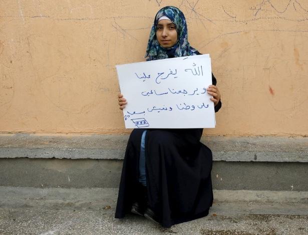 """A refugiada síria Kamer Topalca, 18, segura um cartaz que diz: """"Meu Deus nos salve. Deixe-nos retornar à nossa pátria em segurança. Deixe-nos vivermos felizes"""". Atualmente ela vive no campo de refugiados de Yayladagi, na província de Hatay, na Turquia, perto da fronteira com Síria. A guerra civil na Síria, que já deixou centenas de milhares de mortos, empurra outros tantos para o exílio, entre muitos deles crianças. Os desenhos das crianças do acampamento mostram memórias de suas casas, traumas vividos e esperanças para o seu futuro. Dos 2,3 milhões de refugiados sírios que vivem na Turquia, mais da metade são crianças"""