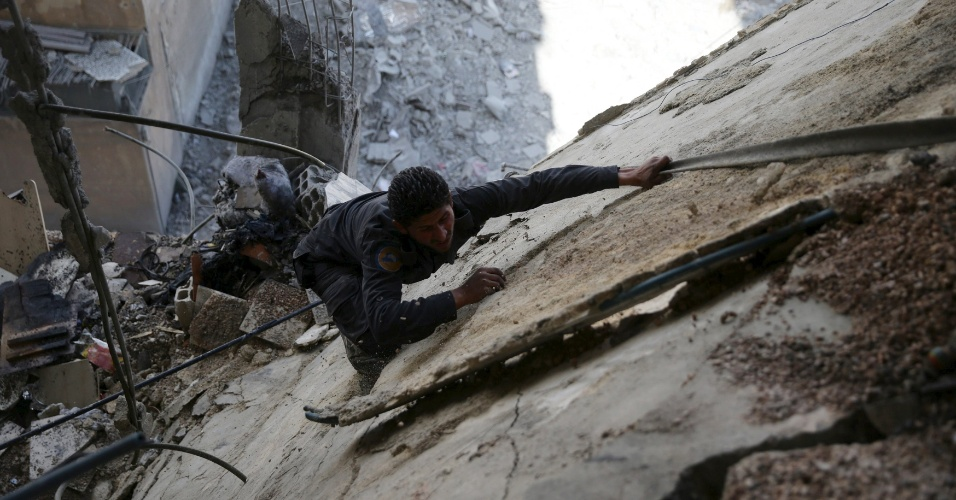 14.fev.2016 - Técnico da defesa civil trabalha sobre destroços após ataques aéreos das forças pró-sírias do governo no bairro rebelde Douma, em Damasco, Síria