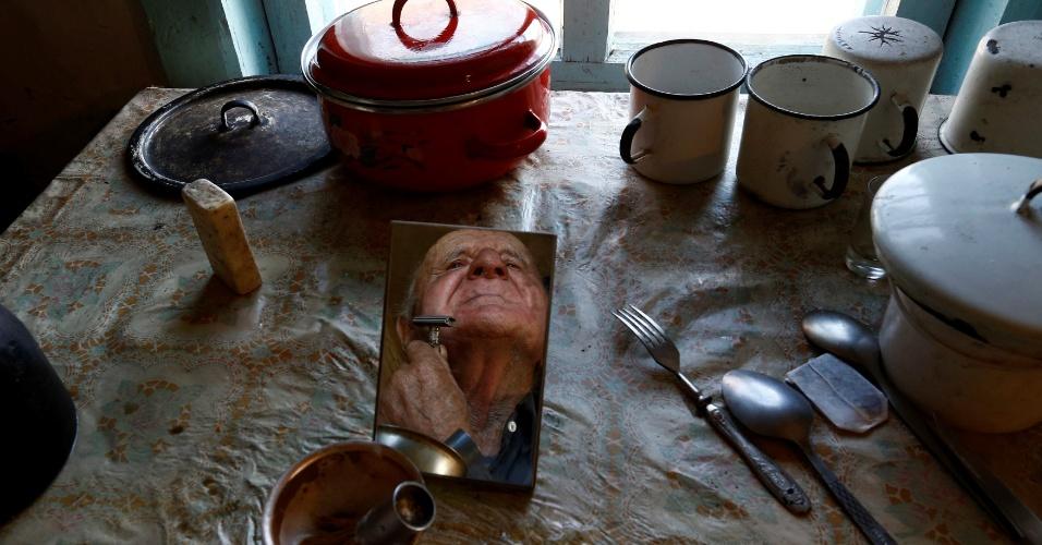 """16.abr.2016 - Ivan Shamyanok, que aparece no espelho fazendo a barba, celebra aniversário de 90 anos tendo sempre vivido em Tulgovichi, vila da Bielorrússia localizada próxima à usina de Chernobyk. Shamyanok conta que segredo da longevidade em uma região potencialmente contaminada por radioatividade é """"nunca ter abandonado a terra natal"""""""