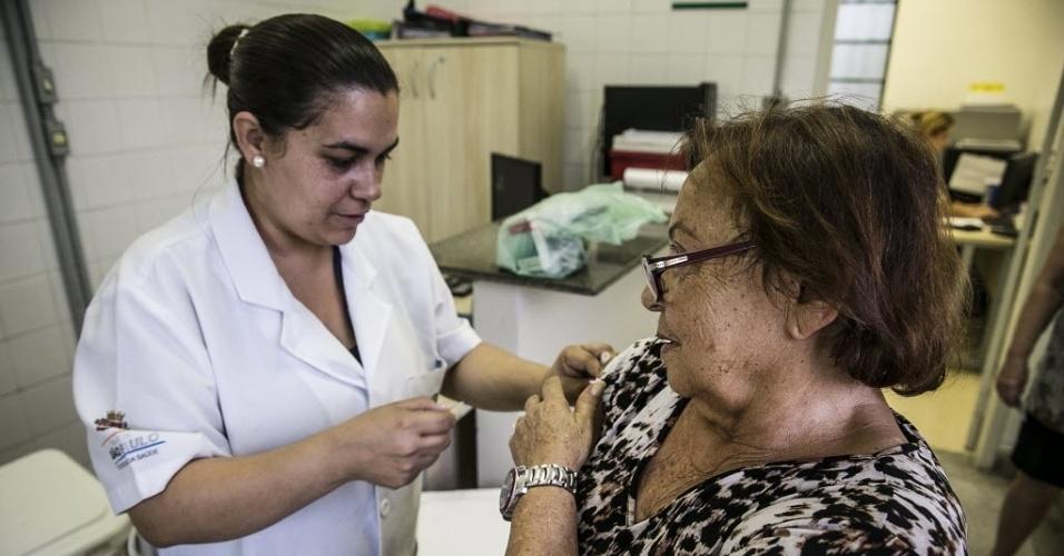 """20.abr.2016 - Aplicada por injeção, a vacina pode causar desconforto no local da aplicação, e um mal-estar leve e passageiro (no máximo 24 horas após a aplicação), como se fosse o início de um resfriado, habitualmente sem sintomas respiratórios. A aposentada Celestina Pacheco de Castro Cardoso, 75, afirma que toma a vacina todos os anos e nunca teve reações. """"Sempre tive bons resultados, nunca mais fiquei gripada"""""""