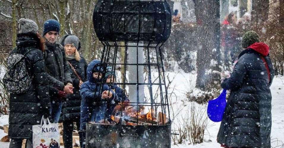 13.jan.2018 - Pessoas se esquentam em um aquecedor a lenha no Parque Sokolniki em Moscou, na Rússia
