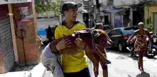 25.jan.2018 - Juan Dias se desespera ao socorrer seu cachorro baleado em tiroteio - Ricardo Moraes/Reuters