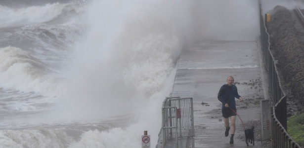 29.jul.2018 - Grandes ondas em ventos fortes atingem orla enquanto um homem corre com seu cachorro em Dawlish, no sudoeste da Grã-Bretanha - Toby Melville/Reuters