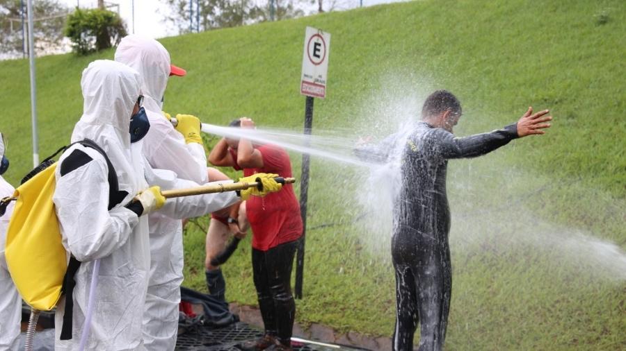 Bombeiros (de branco) dão banho em colegas que estiveram em contato com a lama - Corpo de Bombeiros de MG/Divulgação