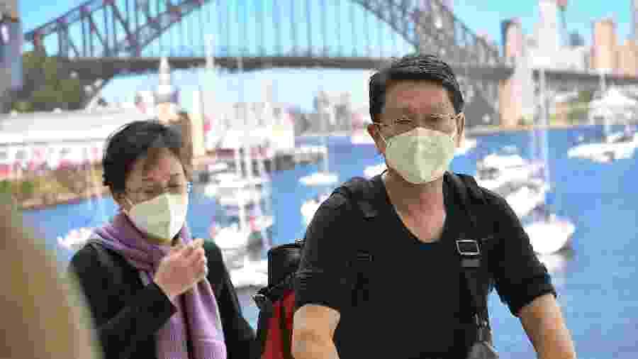 Passageiros vindos da China desembarcam no aeroporto de Sidney, na Austrália, com máscaras para se prevenir contra o coronavírus - Peter Parks/AFP