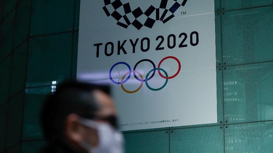 Homem com máscara de proteção passa pelo logo da Olimpíada de Tóquio - ISSEI KATO