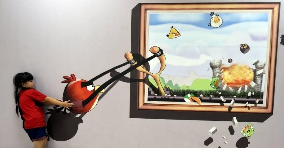 25.ago.2015 - Visitantes brincam com quadro durante exposição de pinturas em 3D na província de Hebei, China