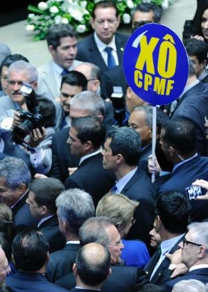 """Deputados seguram placa com """"Xô CPMF"""" antes da presidente Dilma Rousseff fazer o discurso de abertura do ano legislativo no Congresso"""