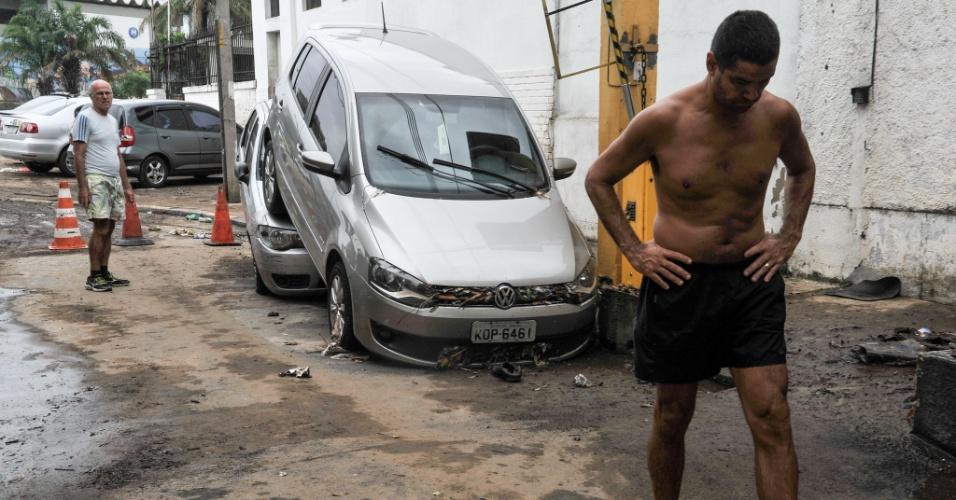 13.mar.2016 - Moradores lamentam estragos causados pela chuva, que alagou truas e deixou carros empilhados na praça da Bandeira, no Rio de Janeiro