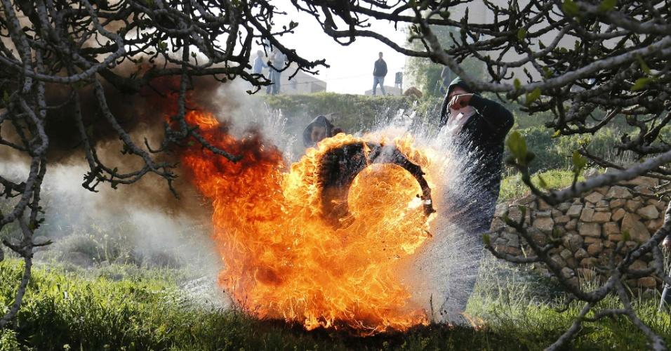 18.mar.2016 - Manifestantes palestinos chutam um pneu em chamas durante confront com forças de segurança israelenses, após um protesto em solidariedade a prisioneiros palestinos em cadeias de Israel. O ato acontece do lado de fora do complexo prisional de Ofer, perto de Betânia, no território ocupado da faixa de Gaza