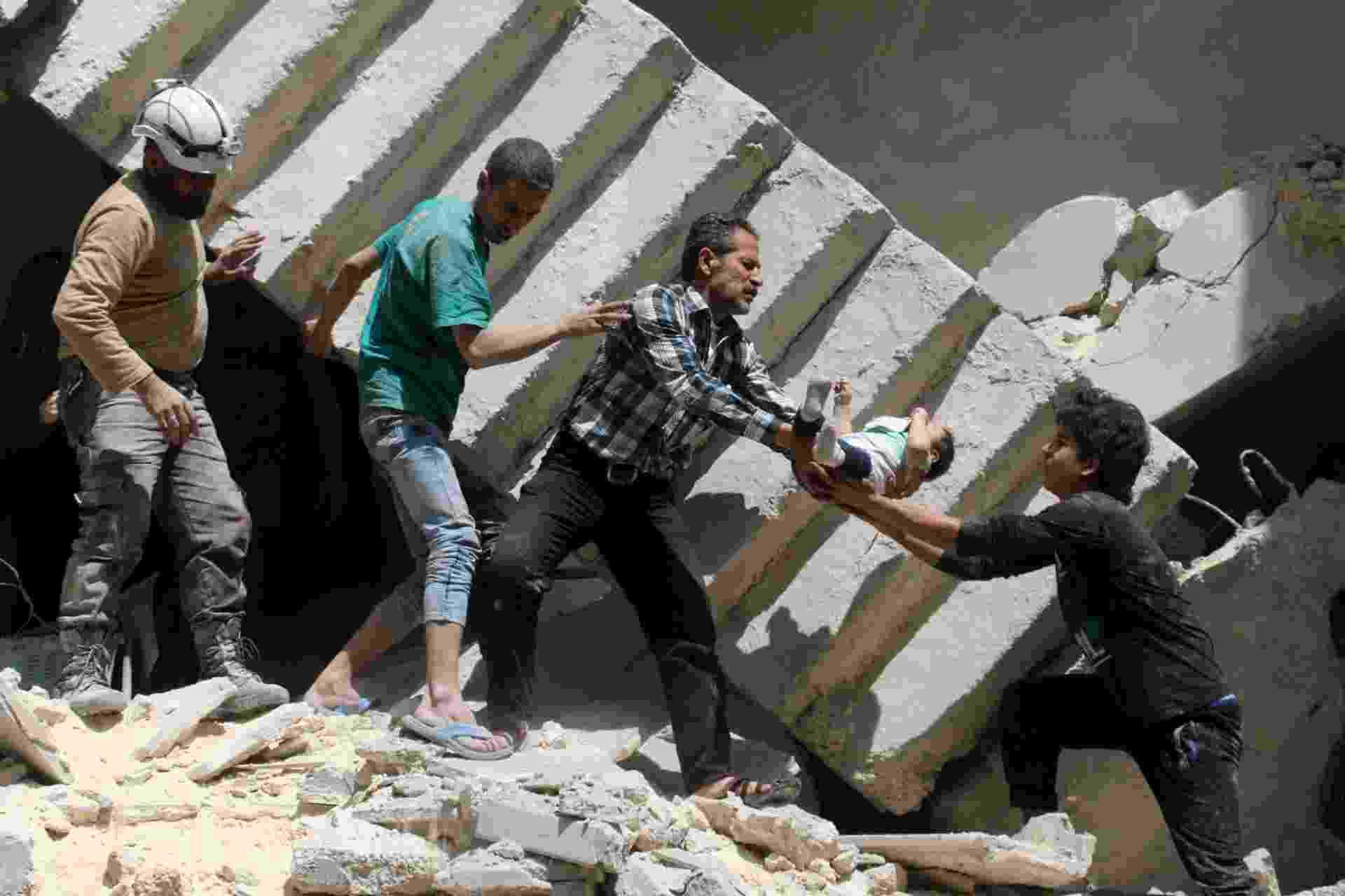 28.abr.2016 - Bebê é carregado depois de bombardeiro em hospital de Aleppo, ao norte Síria. Pelo menos 27 pessoas morreram, entre elas o último pediatra que havia na região controlada pelos rebeldes - Ameer Alhabi/AFP