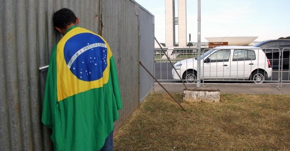 10.mai.2016 - Homem vestido com bandeira do Brasil se encosta no muro colocado no gramado da Esplanada dos Ministérios, em Brasília. A estrutura foi montada para abrigar protestos favoráveis e contrários ao processo de impeachment de Dilma Rousseff, que será votado no Senado nesta quarta-feira (11)