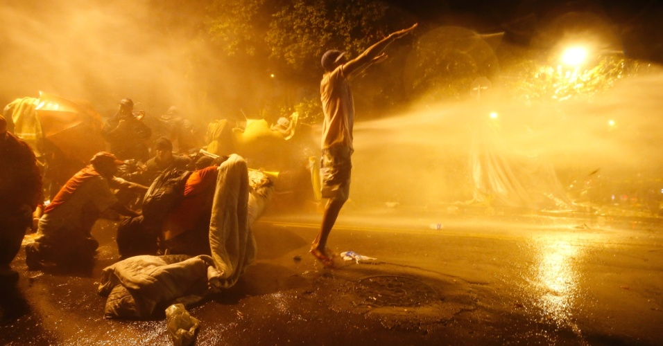 23.mai.2016 - Policiais usam jatos d'água para tentar dispersar manifestantes que estavam acampados em uma praça próxima à residência do presidente interino Michel Temer, na zona oeste de São Paulo. Por volta das 23h45 deste domingo (22), pouco mais de uma hora após ordenarem a saída dos manifestantes, os policiais militares começaram a dispersar o acampamento com bombas de efeito moral, bombas de gás lacrimogênio e jatos d'água
