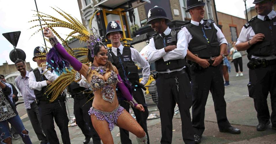 29.ago.2016 - Policiais não seguram a risada e brincam ao ver dançarina durante o Carnaval em Notting Hill, Londres, na Inglaterra