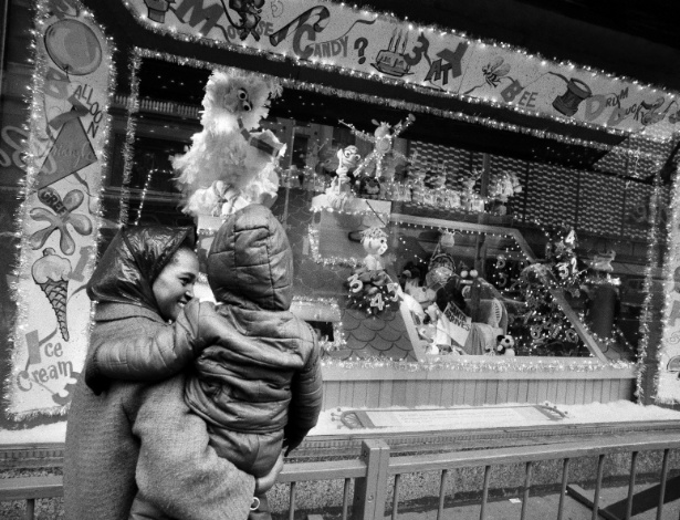 Mulher e seu filho observam vitrine com brinquedos na loja Abraham and Straus em Nova York, em foto tirada semanas antes do Natal de 1971