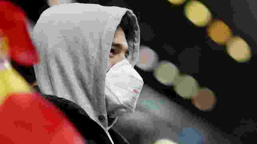Torcedor com másara de proteção em partida do Liverpool - Carl Recine