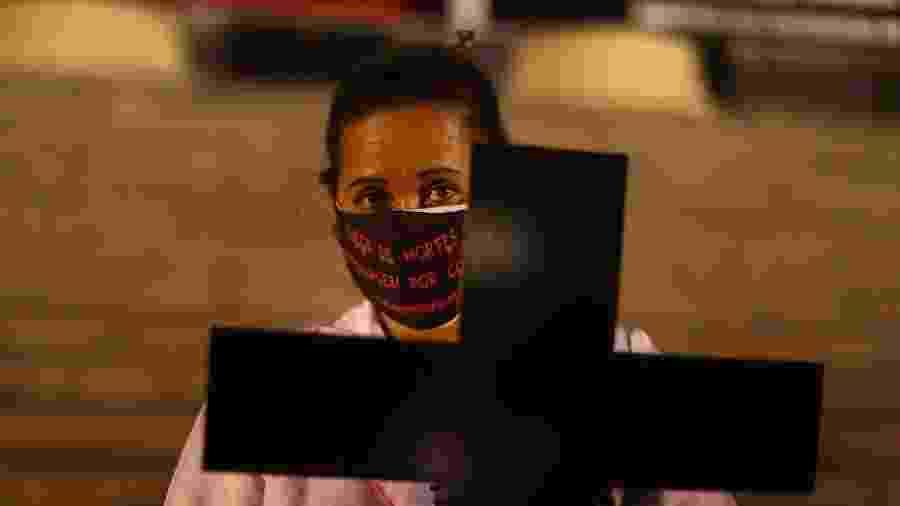"""12.mai.2020 - Profissional de saúde usa uma máscara protetora com a inscrição """"Chega de mortes de enfermagem por covid-19"""" durante homenagem na Alerj a colegas que morreram da doença no Dia da Enfermagem - PILAR OLIVARES/REUTERS"""