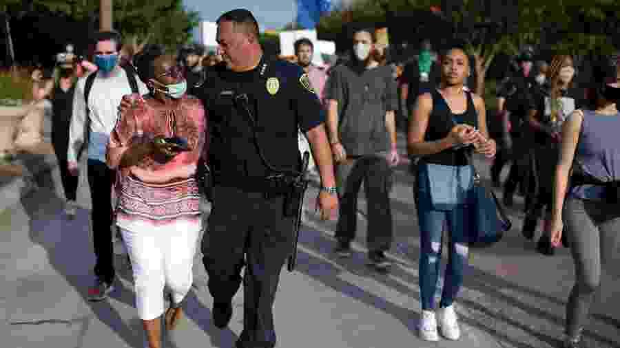 Chefe da Polícia de Houston anda abraçado com uma manifestante durante um protesto que pede justiça para George Floyd - Mark Felix/AFP
