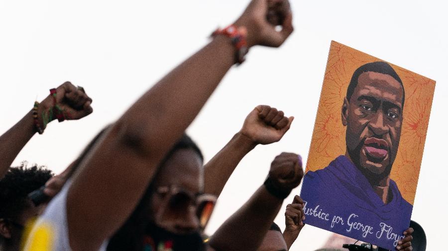 20.abr.2021 - Pessoas levantam os punhos e seguram retrato de George Floyd durante ato após o veredicto do julgamento de Derek Chauvin, em Atlanta, Geórgia (EUA) - Elijah Nouvelage/AFP