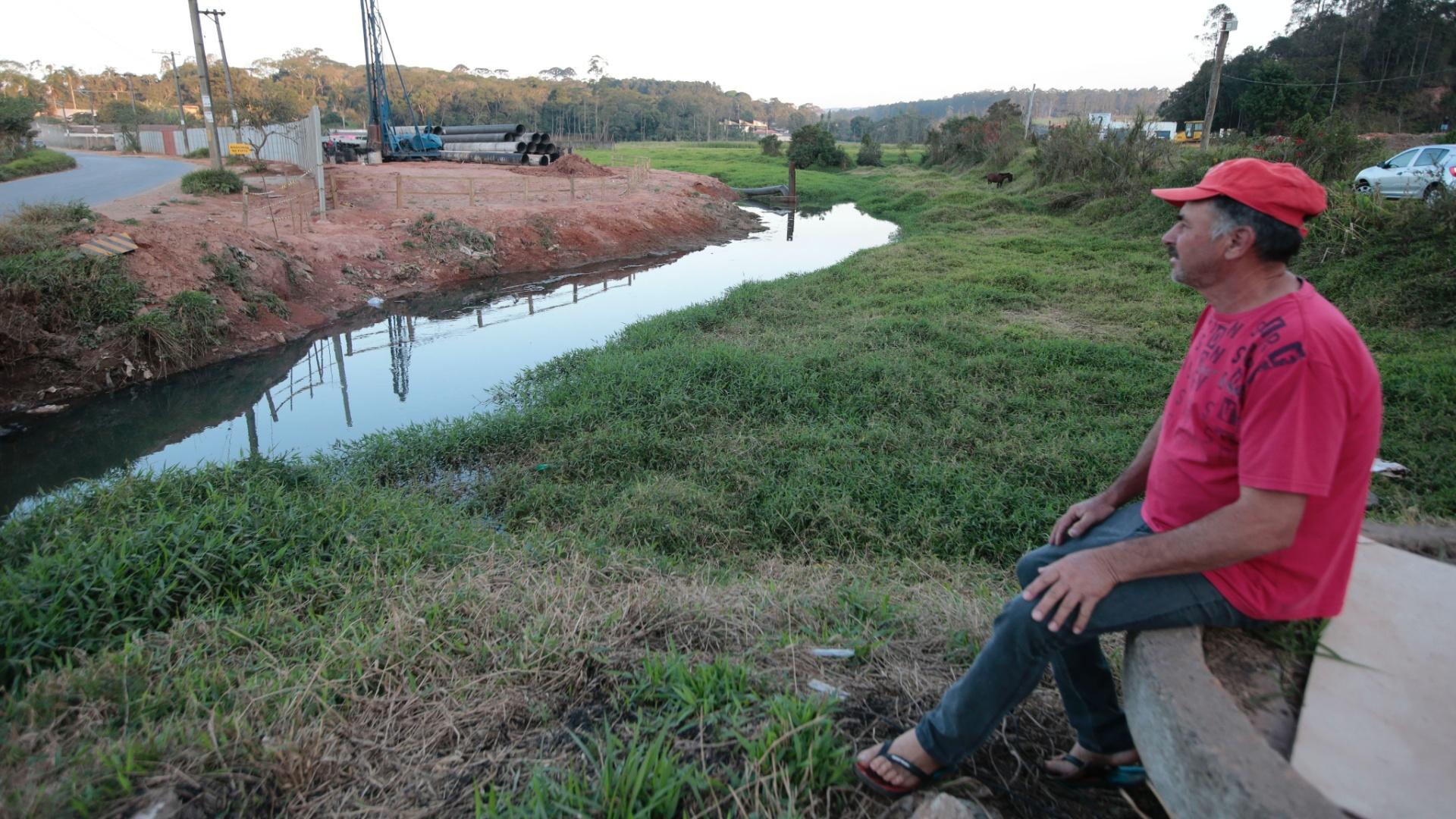 17.ago.2015 - Jair Ramos, 59, observa o nível baixo do rio Guaió, do qual a Sabesp deveria captar água após ter investido R$ 28,9 milhões em uma transposição para