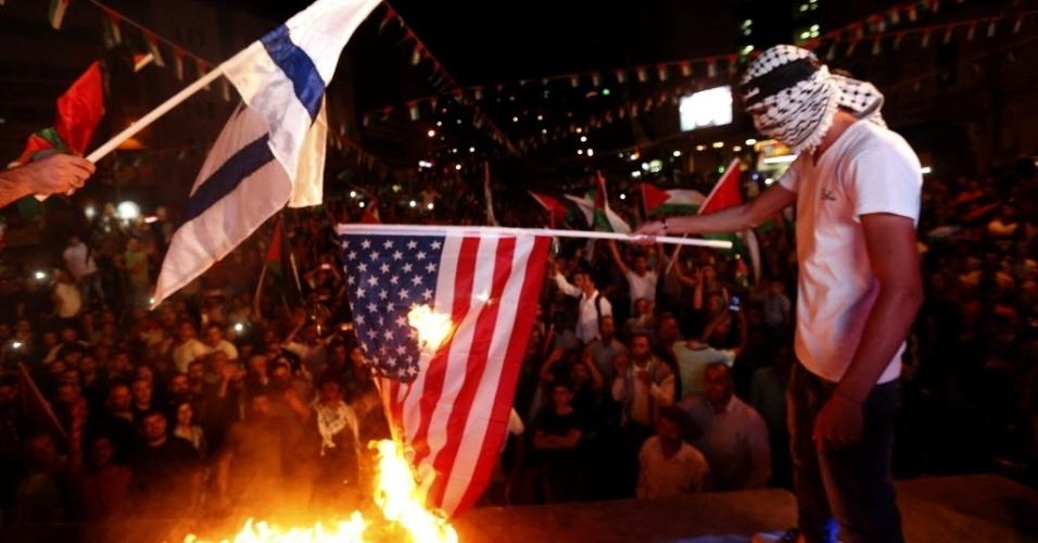 30.set.2015 - Manifestantes queimam bandeiras do Estados Unidos e de Israel na cidade de Nablus, na Cisjordânia, após acompanhar a bandeira da Palestina ser hasteada pela primeira vez na sede da ONU (Organização das Nações Unidas), nos EUA